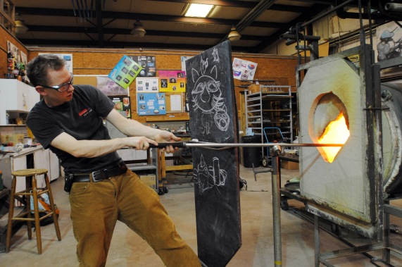 """Jacksonville University Assistant Professor of Glass Brian Frus shapes a glass turtle in his campus studio for an upcoming installation at the Cummer Museum, entitled """"River Table."""" (Christina Kelso/ The Navigator)"""