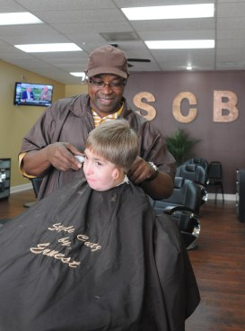 Ernest McHenry jokes with his ten-year-old regular customer Andrew, while cutting his hair his shop, Style Cutz Barber Shop at 305 Blanding Blvd, on Tuesday March 31. (Christina Kelso/ Clay Today)