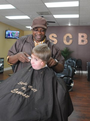 Earnest McHenry jokes with his ten-year-old regular customer Andrew, while cutting his hair his shop, Style Cutz Barber Shop at 305 Blanding Blvd, on Tuesday March 31. (Christina Kelso/ Clay Today)