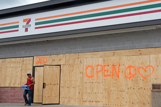 A man carries a case of water out of a boarded St. Augustine Beach 7-Eleven gas station on Friday, September 8, 2017, in preparation for Hurricane Irma. (Christina Kelso/ The St. Augustine Record)