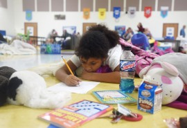 Eight-year-old Arianna Petrocine draws on the floor of the St. Johns County Pet Friendly Shelter at Timberlin Creek Elementary School on Thursday October 6, 2016 after evacuating her Crescent Beach home with her parents, Hazel Petrocine and Richard Petrocine, and their shih tzu Romeo in preparation for Hurricane Matthew. (Christina Kelso/ The St. Augustine Record)