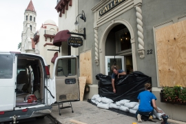 Tripp Harrison and his daughter and gallery director McKenzie Harrison place sandbags at the front entrance of Tripp Harrison Studio and Gallery on Cathedral Place on Saturday, September 9, 2017, in preparation for Hurricane Irma. Tripp Harrison said that the gallery has flooded six times in 12 years, only opening approximately three months ago after being damaged in Hurricane Matthew. (Christina Kelso/ The St. Augustine Record)