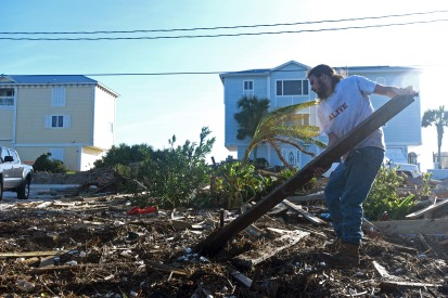 Max Sheppard helps to clear debris from his aunt's Vilano Beach home on Sunday October 9, 2016, while she sleeps inside. Sheppard, a student at Florida Atlantic University, drove up from his home in Miami to help when his family sent him photographs of the destruction they found left behind by Hurricane Matthew after returning from evacuation Saturday morning. (Christina Kelso/ The St. Augustine Record)