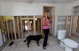 Davis Shores resident Jill Nicolino with her dog Zac inside of her gutted Coquina Avenue home on Friday, December 2, 2016. Nicolino, who has owned the house for less than a year, is facing difficulty navigating the rebuilding process in the wake of Hurricane Matthew. (Christina Kelso/ The St. Augustine Record)
