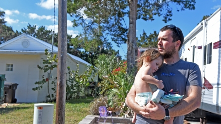 Davis Shores resident Tyne Anderson stands in the yard of his Arricola Avenue home with his two-year-old daughter Presley Anderson on Thursday, February 2, 2017. Anderson's family of four is currently living in an RV while working through repairs to their home, which was damaged in Hurricane Matthew. (Christina Kelso/ The St. Augustine Record)