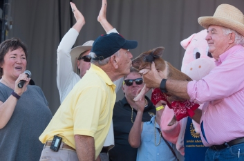 Winner of Learn to Read St. Johns County's Kiss the Pig contest Rick Ezequelle smooches Wilber the piglet on the snout during the Rhythm and Ribs festival at Francis Field on Saturday, April 1, 2017. (Christina Kelso/ The St. Augustine Record)