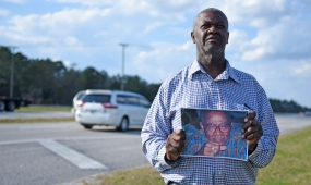 James Allen Jr. holds a photograph of his father, James Allen Sr., on Tuesday, February 7, 2017, on the side of northbound U.S. 1 near where the 81-year-old was struck and killed while walking on Jan. 13 in what authorities say was a hit-and-run collision. (Christina Kelso/ The St. Augustine Record)