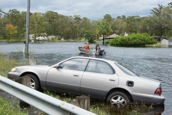 St. Augustine residents James Howery and Shane Manning use a small motorboat to cross the flooded parking lot of Outback Crab Shack on State Road 13 to check on their sailboat, which was left tied up on the adjacent Six Mile Creek, on Monday, September 11, 2017, in the afternoon following Hurricane Irma. (Christina Kelso/ The St. Augustine Record)