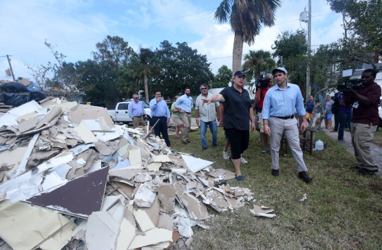Carol Saviak walks with Sen. Marco Rubio past a pile of drywall stripped from her home in Davis Shores on Wednesday October 12, 2016, before giving him a tour of the house's interior, which had to be largely gutted after damage from Hurricane Matthew. (Christina Kelso/ The St. Augustine Record)