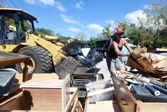 Volunteer Lura Scarpitti helps to load debris from Bob and Joan Stanton's Treasure Beach home, which flooded in Hurricane Matthew, into a truck for disposal during a neighborhood organized cleanup on Wednesday October 19, 2016. (Christina Kelso/ The St. Augustine Record)