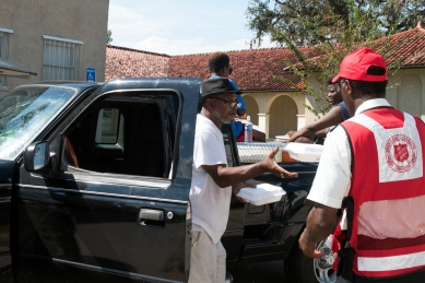Dennis Sims, a Salvation Army mission specialist from Goldsboro, North Carolina, hands warm boxed lunches to Hastings resident Edward Grayer Sr. and his family on Thursday, September 14, 2017. The Salvation Army distributed free breakfast, lunch and dinner to residents in front of the Hasting Branch Library, offering some relief in the area heavily impacted by flooding from Hurricane Irma. (Christina Kelso/ The St. Augustine Record)