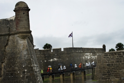 Shielding themselves with ponchos and umbrellas, a line of visitors crosses into the Castillo de San Marcos during a rainstorm on Tuesday, June 6, 2017. (Christina Kelso/ The St. Augustine Record)