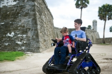 Toddler Rhett Natto, son of local U.S. Marine veteran Chris Natto, sits on his father's lap to steer his new all-terrain wheelchair around the grounds of the Castillo de San Marcos on Wednesday, June 28 2017. Chris Natto, who was partially paralyzed in a parachute accident during a Feb. 2016 training exercise at Fort Bragg, was presented with the chair on Wednesday by Freedom Alliance, a national organization supporting American military veterans and their families. The chair is designed to provide Natto the mobility needed to more easily join his family in outdoor adventures, such as beach visits and trail walking. (Christina Kelso/ The St. Augustine Record)