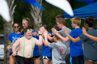 """Fifteen-year-old Kevin Harrison high-fives a cheering line of fans on Saturday, August 5, 2017, after competing in the St. Johns County Special Olympics Swimming Competition at the Solomon Calhoun Center. Twenty county athletes, from nine-years-old to adult, participated in the fifth annual event. Under the team name, the """"St. Johns Splash,"""" the athletes have trained together for the competition since June. (Christina Kelso/ The St. Augustine Record)"""