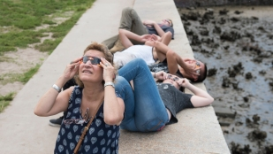 Peering up to the sky through protective glasses, people view the 2017 solar eclipse from the Castillo de San Marcos on Friday, August 18, 2017. (Christina Kelso/ The St. Augustine Record)