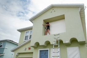 St. Augustine Beach resident Nancy Cubbedge seals a second-story window of her home on Friday, September 8, 2017, in preparation for Hurricane Irma. Mandatory evacuations begin in the area at 6 a.m. on Saturday. Cubbedge and her family plan to leave for Alabama tomorrow morning to stay with relatives. (Christina Kelso/ The St. Augustine Record)