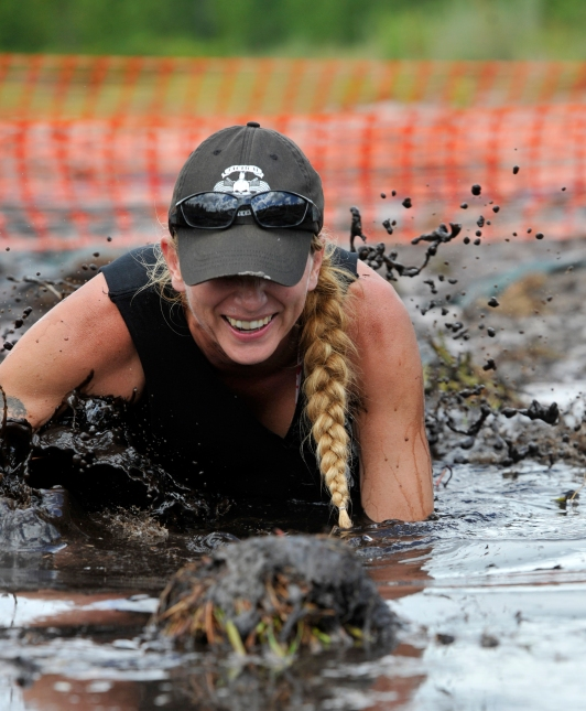 Charisa Butz, co-organizer of the St. Johns Family Festival and Tactical Elite Warrior Challenge 5K mud run, crawls through the course's first obstacle on Sunday August 28, 2016. The inaugural event took place August 27 and 28 at the St. Augustine Flea Market with a portion of proceeds benefiting the Brave-Aid wounded warrior assistance fund. (Christina Kelso/ The St. Augustine Record)